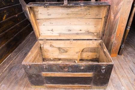 treasure trove: Old wooden sailors trunk with the lid open standing on a wooden deck of an antique sailing vessel, close up high angle view