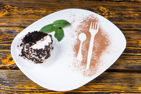 decadent: High Angle View of Decadent Dessert Coated in Chocolate Shavings and Served on Plate with Mint Leaf Garnish and Utensil Outlines Dusted in Cocoa and Resting on Wooden Table Surface Stock Photo