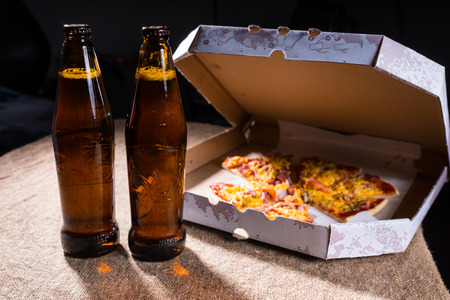 out of the box: Side View of Bottles of Beer on Burlap Covered Table Beside Cardboard Take Out Box of Pizza with Open Lid Stock Photo