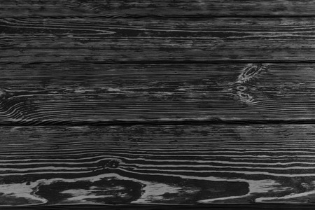 floorboards: Stained dark wood boards background texture with a wood grain pattern in a full frame view