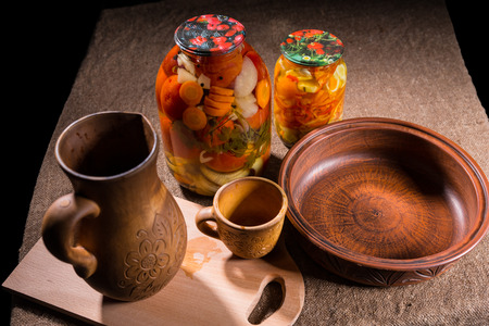 preserves: High Angle View of Jars of Pickled Vegetable Preserves on Table Surface Next to Carved Wooden Handicrafts - Wood Pitcher, Cup, Bowl and Wooden Cutting Board with Copy Space Stock Photo