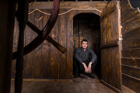 sharply: Portrait of Young Business Man Dressed Sharply and Sitting on Floor in Open Doorway of Antique Wooden Sailing Ship, Leading to Interior Living Quarters and Cabin Area Stock Photo