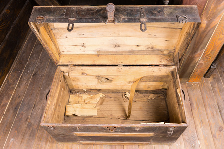 treasure trove: Empty old vintage wooden chest with the lid open standing on a wooden floor , high angle view looking inside