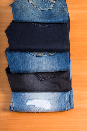 pantalones abajo: Vista elevada de Blue Jeans - Mirar hacia abajo al dril de algodón de los pantalones de diferentes colores lavados y Estilos abrieron en abanico en superficie de madera en la tienda de ropa de visualización Foto de archivo