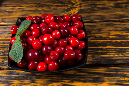 Bowl of ripe red cherries garnished with fresh mint for a tasty snack or for use as a cooking and baking ingredient, view from above on a wooden table with copyspace Stock fotó