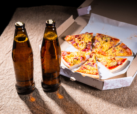 out of the box: Two Bottles of Beer on Burlap Covered Table Next to Artisan Pizza Divided into Slices Arranged in Cardboard Take Out Box Stock Photo
