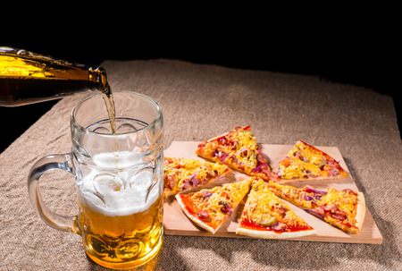 bottled beer: Pouring Bottled Beer into Glass Mug with Meal of Fresh Baked Pizza Arranged in Slices on Wooden Cutting Board on Burlap Covered Table