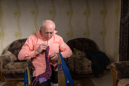 natty: Disabled old man is choosing a tie