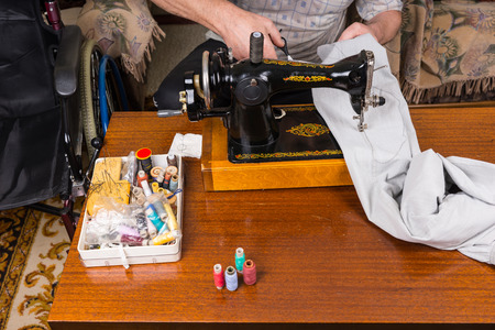 mending: High Angle View of Unidentifiable Man Mending Pants Using Old Fashioned Manual Sewing Machine on Table Surrounded by Sewing Supplies Stock Photo