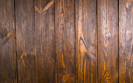 floorboards: Full frame of dark brown wooden floorboards shot from directly above, with knots in wood and gaps between boards