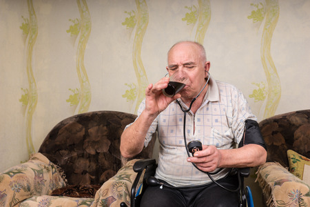 special needs: Bald Senior Man with Special Needs on his Wheelchair in the Living Room, Reading a Sphygmomanometer While Drinking a Glass of Healthy Juice Drink.