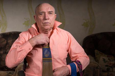 natty: Handsome senior sad man is trying on a tie