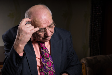 oldage: Close up Contemplative Old Businessman in Formal Suit, Scratching his Bald Head While Looking Down.