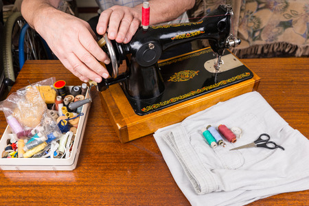 Close Up of Senior Man Using Old Fashioned Manual Sewing Machine Surrounded by Sewing Materials and Various Threads