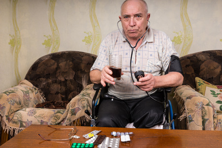 special needs: Senior Bald Man with Special Needs, Sitting on his Wheelchair at the Living Room, Looking at the Camera While Holding a Healthy Juice Drink and BP Apparatus