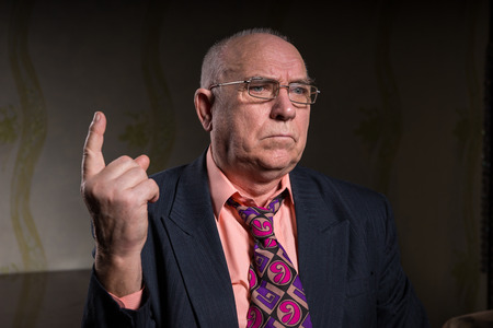 formal attire: Close up Senior Bald Businessman in Formal Attire, Pointing his Finger Up While Looking Into Distance with Serious Facial Expression.