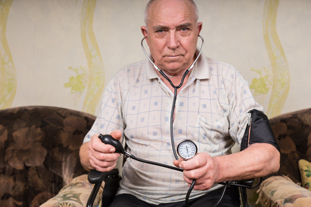 sphygmomanometer: Senior Bald Man with Special Needs, Sitting on his Wheelchair and Holding Sphygmomanometer and Stethoscope Apparatus, Looking Straight at the Camera. Stock Photo