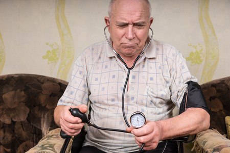 auscultation: Disabled frowning senior man monitoring his blood pressure through auscultation with a stethoscope and an aneroid sphygmomanometer while sitting in a wheelchair at home