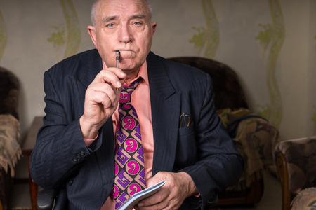 inscrutable: Close up Middle Aged Bald Businessman Holding Pen to Corner of his Mouth and Small Notes, Looking at the Camera Seriously