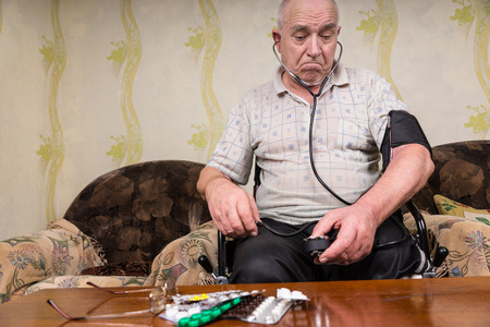 aneroid: Thoughtful Old Bald Man with Blood Pressure Apparatus, Sitting on his Wheelchair In the Living Room with his Medicines on top of the Table.
