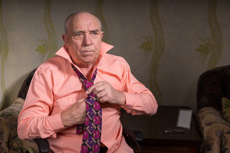natty: Serious old man tying his tie