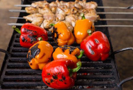 griddle: Close Up of Grilling Fresh Whole Red and Orange Peppers and Meat Skewer Kebabs on Outdoor BBQ Grill Stock Photo