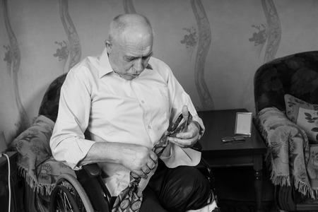 oldage: Disabled sad old man remember how to tie a tie Stock Photo