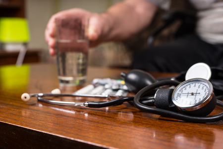special needs: Close up Blood Pressure Apparatus on Top of a Wooden Table with Medicines and a Glass of Water for an Elderly with Special Needs.