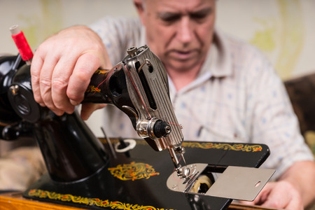 oldage: Close Up of Senior Man Inspecting Bottom of Old Fashioned Sewing Machine in Living Room at Home