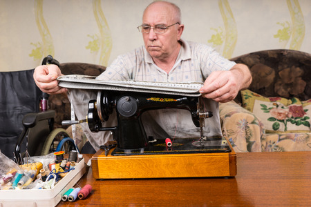oldage: Senior Man at Old Fashioned Sewing Machine Measuring Pant Legs at Home in Living Room