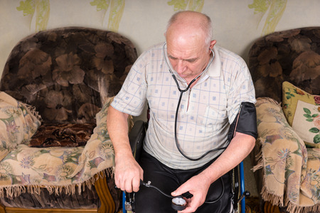 aneroid: High Angle View of a Senior Bald Man Sitting on his Wheelchair, Checking his Blood Pressure Alone Using Apparatus in the Living Room. Stock Photo