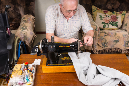 mending: High Angle View of Senior Man Mending Pants with Old Fashioned Manual Sewing Machine at Home in Living Room