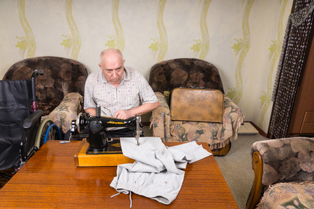 mend: High Angle View of Senior Man Using Old Fashioned Manual Sewing Machine to Mend Pants at Home in Living Room with Wheelchair Close By