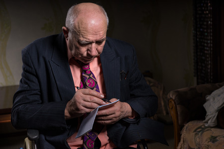 sombre: Old Bald Businessman in Formal Wear Sitting on his Wheelchair, Writing on his Small Notebook Seriously