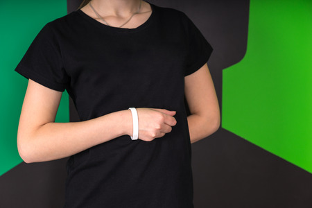 concealing: Mid section front view of young female wearing black t-shirt and white wristband, hand in a fist against abdomen, other hand behind back on a green and black background.