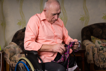 natty: Disabled old man is focused on a tie