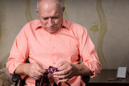natty: Senior man is focused on a tie Stock Photo