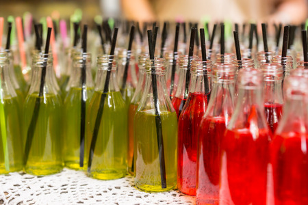 Refreshments: Close Up of Gourmet Red and Green Sodas in Glass Bottles with Black Straws