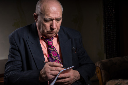 introspective: Close up Senior Bald Businessman in Business Suit, Taking Down Notes with Serious Facial Expression.