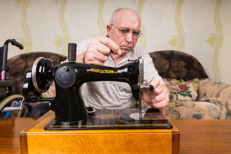 bald head: Serious Senior Tailor Man with Bald Head, Putting Thread on his Manual Sewing Machine Inside his House. Stock Photo