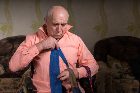 natty: Handsome senior sad man is trying on a blue tie