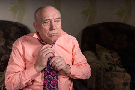 natty: Sad old man tying his tie