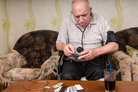 bp: Bald Middle Aged Man on his Wheelchair, Checking his Medicines While Holding a BP Apparatus at the Living Room.