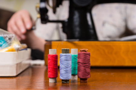 old spools: Close Up of Spools of Colorful Thread on Table in front of Person Using Old Fashioned Manual Sewing Machine in Background