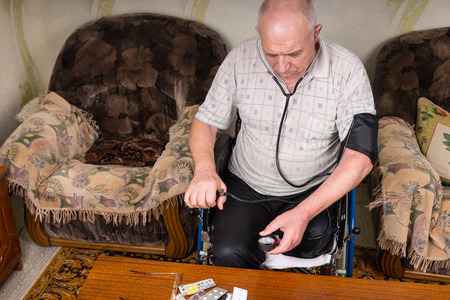 aneroid: High Angle View of an Elderly Man with Special Needs Sitting on his Wheelchair, Checking his Blood Pressure Using a Manual BP Apparatus inside his House.