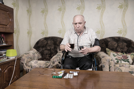 special needs: Pensive Elderly Man with Special Needs on his Wheelchair, Looking Straight at his Medicines on the Table While Holding a Glass of Juice and Sphygmomanometer for Blood Pressure. Stock Photo