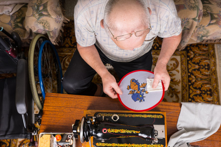 oldage: High Angle View of Senior Man Admiring and Inspecting Needlepoint Work on Wall Hanging Craft and Sitting Next to Old Fashioned Sewing Machine in Home with Wheelchair Stock Photo