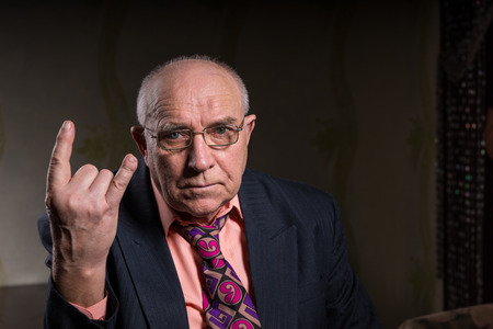 devil horns: Elderly man making a horns gesture depicting heavy metal rock music or the sign of the devil, seated head and shoulders portrait on a dark background with copyspace