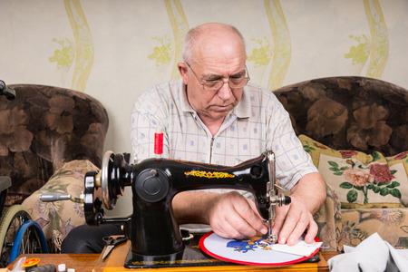 maquinas de coser: Hombre mayor serio utilice gafas de Trabajo sobre Needle Point Arte de la pared que cuelga Usando vieja m�quina de coser de moda en el hogar en la sala de estar