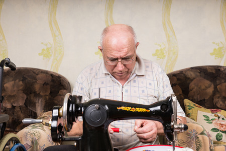 oldage: Serious Senior Man Looking Down at Spool of Red Thread and Threading Old Fashioned Manual Sewing Machine at Home in Living Room Stock Photo